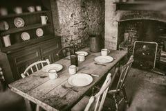 Φτωχό εσωτερικό αγροτών από το 19ο αιώνα, τραπεζαρία με τον καθορισμένο ξύλινο πίνακα και εστία, φωτογραφία ύφους σεπιών στοκ εικόνα