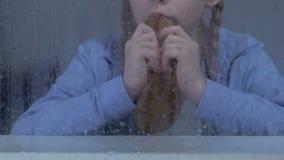 Φτωχό κορίτσι που τρώει το ψωμί πίσω από το βροχερό παράθυρο, επισφαλές κοινωνικό στρώμα, ορφανοτροφείο απόθεμα βίντεο
