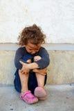 Φτωχό, λυπημένο παιδί ενάντια στο συμπαγή τοίχο Στοκ φωτογραφία με δικαίωμα ελεύθερης χρήσης