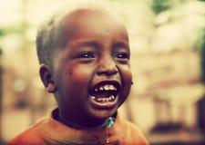 Φτωχό μικρό παιδί που γελά με τα έντομα τσετσέ σε τον. Τανζανία, Αφρική στοκ εικόνα με δικαίωμα ελεύθερης χρήσης