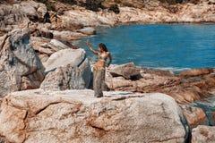 Φυλετικός χορευτής κοιλιών γυναικών που χορεύει στην παραλία πετρών στοκ εικόνες με δικαίωμα ελεύθερης χρήσης