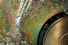Φυσαλίδες στη χαλασμένη επιφάνεια του CD Μακρο αφηρημένο κατασκευασμένο backgroun στοκ φωτογραφία