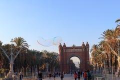 Φυσαλίδα σαπουνιών μπροστά από τη θριαμβευτική αψίδα Arc de Triomf και επιχειρήσεις περιπάτων Passeig de Lluis στη Βαρκελώνη Στοκ Εικόνες