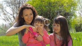 Φυσαλίδες χτυπήματος Mom και κορών Οικογένεια στο πάρκο Τα παιδιά με το mom παίζουν με τις φυσαλίδες απόθεμα βίντεο