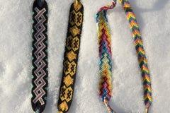 Φυσικά βραχιόλια της φιλίας σε μια σειρά, ζωηρόχρωμα υφαμένα βραχιόλια φιλίας, υπόβαθρο χιονιού, χρώματα ουράνιων τόξων, ελεγμένο Στοκ Εικόνες