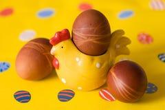Φυσικά οργανικά αυγά εστέρα με τη διακόσμηση κοτών και το κίτρινο υπόβαθρο προετοιμασίες Πάσχας Στοκ Φωτογραφίες
