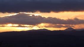 Φυσικά σύννεφα ηλιοβασιλέματος πέρα από ξεσκονισμένους τους χιόνι λόφους στο UK απόθεμα βίντεο