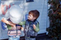 Φυσικές εικόνες μιας ευτυχούς τετραμελούς οικογένειας που έχει τη διασκέδαση outsiade και που τρώει το νήμα ζάχαρης οικογένεια τέ στοκ φωτογραφίες με δικαίωμα ελεύθερης χρήσης