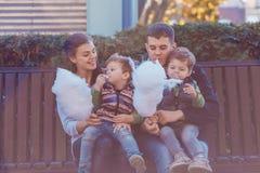 Φυσικές εικόνες μιας ευτυχούς τετραμελούς οικογένειας που έχει τη διασκέδαση outsiade και που τρώει το νήμα ζάχαρης οικογένεια τέ στοκ εικόνες