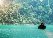 Φυσική άποψη της μικρής ξύλινης βάρκας που επιπλέει στον πράσινο ποταμό του φράγματος Ratchaprapa, εθνικό πάρκο Khao Sok, Σουράτ  Στοκ Εικόνα