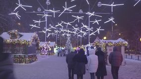 Φυσική άποψη του διακοσμημένου πάρκου χειμερινών πόλεων τη νύχτα Περίπατος ανθρώπων και μωρών στην πόλη πάγου κατά τη διάρκεια τω απόθεμα βίντεο