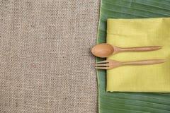 Φυσική κουζίνα έννοιας, ξύλινα δίκρανο και κουτάλι στην κίτρινη πετσέτα στο πράσινο φύλλο μπανανών Στοκ φωτογραφίες με δικαίωμα ελεύθερης χρήσης