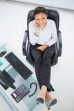 Φυσική νέα μελαχροινή μαλλιαρή επιχειρηματίας που κάνει ένα τηλεφώνημα Στοκ εικόνα με δικαίωμα ελεύθερης χρήσης