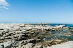 Φυσική παραλία πετρών πέρα από τον μπλε seacoast ορίζοντα Στοκ Φωτογραφίες
