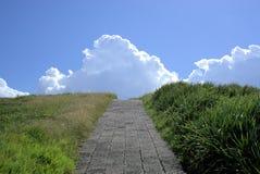 Φυσική πορεία στο λόφο που πηγαίνει προς τα σύννεφα στον ουρανό στοκ φωτογραφία