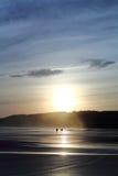 Φυσική σκιαγραφία του ζεύγους με το σκυλί που περπατά στην αμμώδη παραλία στο ζωηρόχρωμο θερινό ουρανό ανατολής με την αντανάκλασ στοκ εικόνες