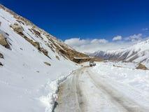 Φυσική χειμερινή άποψη από το δρόμο ασφάλτου στα βουνά που καλύπτονται με το χιόνι Στοκ Φωτογραφία