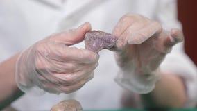 Φυσικός αμέθυστος πετρών ή ένα άλλο μετάλλευμα, πέτρα Ο άγριος αμέθυστος στο θηλυκό παραδίδει τα άσπρα γάντια Πέτρα βράχου στα χέ φιλμ μικρού μήκους