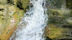 Φυσικός καταρράκτης στις πράσινες πέτρες, κινηματογράφηση σε πρώτο πλάνο φιλμ μικρού μήκους