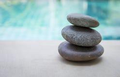 Φυσικός σωρός πετρών της Zen πέρα από το θολωμένο μπλε υπόβαθρο πισινών Στοκ Εικόνα
