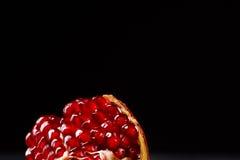 Φυσικός, φρέσκος γρανάτης για τα επιδόρπια και τα ποτά σε ένα μαύρο υπόβαθρο Το κόκκινο ρόδι ανάλυσε στα μέρη Στοκ φωτογραφία με δικαίωμα ελεύθερης χρήσης