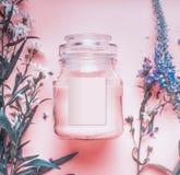 Φυσικό βάζο καλλυντικών με κρέμα ή την αποφλοίωση κρητιδογραφιών τη ρόδινη, βοτανικά φύλλα και άγρια λουλούδια, κενή ετικέτα για  Στοκ Φωτογραφίες