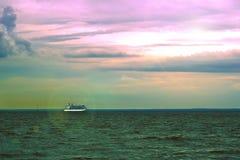 Φυσικό ηλιοβασίλεμα ουρανού με ένα κρουαζιερόπλοιο που πλέει μακριά με τον ορίζοντα με την πράσινη χλόη στο πρώτο πλάνο Σύλληψη δ Στοκ Εικόνες