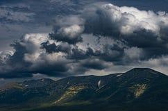 Φυσικό θυελλώδες cloudscape πέρα από τις αιχμές βουνών με τα ηλιόλουστα κυριώτερα σημεία στις κλίσεις Στοκ Εικόνα