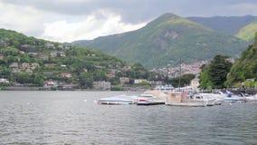 Φυσικό ιταλικό χωριό της μεγάλης λίμνης βουνών με τα σκάφη που δένονται, Como φιλμ μικρού μήκους