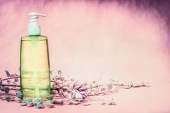 Φυσικό καλλυντικό μπουκάλι προϊόντων με το πράσινο λοσιόν ή το τονωτικό υγρό με τα φρέσκα χορτάρια και λουλούδια στο ρόδινο υπόβα Στοκ Εικόνες