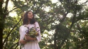 Φυσικό κορίτσι ομορφιάς με την ανθοδέσμη των λουλουδιών υπαίθριων στην έννοια απόλαυσης ελευθερίας απόθεμα βίντεο