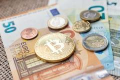 Φυσικό νόμισμα Bitcoin και ευρο- νομίσματα που κάθονται στα ευρο- τραπεζογραμμάτια Στοκ φωτογραφίες με δικαίωμα ελεύθερης χρήσης
