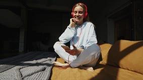 Φυσικό ξανθό άκουσμα χαμόγελου τη μουσική στην κρεβατοκάμαρα απόθεμα βίντεο