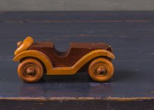 Φυσικό ξύλινο παλαιό παιχνίδι αυτοκινήτων στο ξύλινο γκρίζο υπόβαθρο, vintag Στοκ Εικόνες