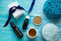 Φυσικό οργανικό ουσιαστικό πετρέλαιο μπουκαλιών σαπουνιών και αλατισμένο βοτανικό λουτρό θάλασσας σε έναν μπλε ξύλινο πίνακα στοκ φωτογραφία