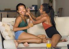 Φυσικό πορτρέτο τρόπου ζωής δύο γυναικών, ένα ευτυχές κορίτσι που βάζουν το δαχτυλίδι αυτιών στο νέο όμορφο και εξωτικό SMI φίλων στοκ φωτογραφία