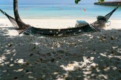 Φυσικό τοπίο της ηλιόλουστης τροπικής ωκεάνιας παραλίας με την άσπρη άμμο και μια αιώρα Ειδυλλιακό τοπίο του παραθαλάσσιου θερέτρ στοκ φωτογραφίες