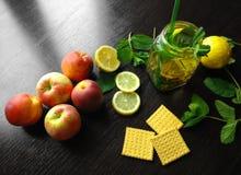 Φυσικό φρέσκο τσάι σε ένα φλυτζάνι στον ξύλινο πίνακα με το λεμόνι και τα μήλα Στοκ Εικόνες