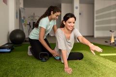 Φυσιοθεραπευτής που βοηθά τη νέα καυκάσια γυναίκα με την άσκηση στοκ εικόνες