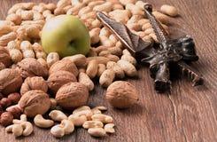 Φυστίκια, ξύλα καρυδιάς σε ένα ξύλινο υπόβαθρο, καρυοθραύστης, πράσινα μήλα Στοκ φωτογραφία με δικαίωμα ελεύθερης χρήσης