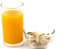 Φυστίκια σε ένα πιάτο γυαλιού και ένα ποτήρι του χυμού από πορτοκάλι απομονωμένο ο Στοκ φωτογραφία με δικαίωμα ελεύθερης χρήσης