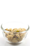 Φυστίκια σε ένα πιάτο γυαλιού, που απομονώνεται στο άσπρο υπόβαθρο Στοκ φωτογραφία με δικαίωμα ελεύθερης χρήσης