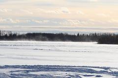 Φυσώντας και παρασύρον χιόνι πέρα από μια ανοικτή λίμνη Στοκ Φωτογραφία
