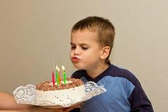 Φυσώντας κερί πέμπτων γενεθλίων εορτασμού αγοριών γιων κέικ Στοκ Φωτογραφίες