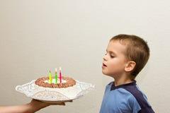 Φυσώντας κερί πέμπτων γενεθλίων εορτασμού αγοριών γιων κέικ Στοκ Εικόνα