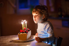 Φυσώντας κεριά αγοριών παιδάκι στο κέικ γενεθλίων Στοκ Φωτογραφία