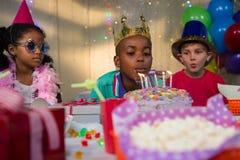 Φυσώντας κεριά αγοριών στο κέικ γενεθλίων Στοκ Εικόνες