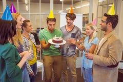 Φυσώντας κεριά επιχειρηματιών στο κέικ γενεθλίων της στοκ εικόνα