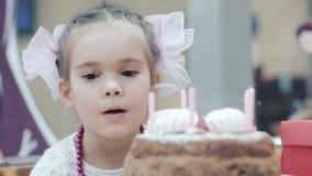 Φυσώντας κεριά μικρών κοριτσιών στο κέικ γενεθλίων φιλμ μικρού μήκους