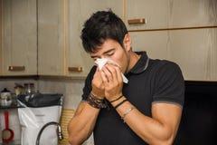 Φυσώντας μύτη νεαρών άνδρων στον ιστό στοκ φωτογραφία με δικαίωμα ελεύθερης χρήσης